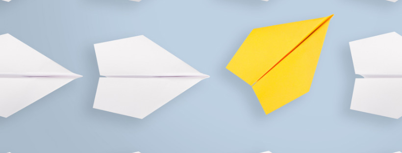 A paper plane going in a different direction from the others